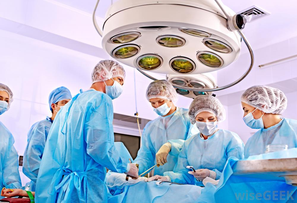 group-of-surgeons-around-patient-on-bed-with-overhead-light