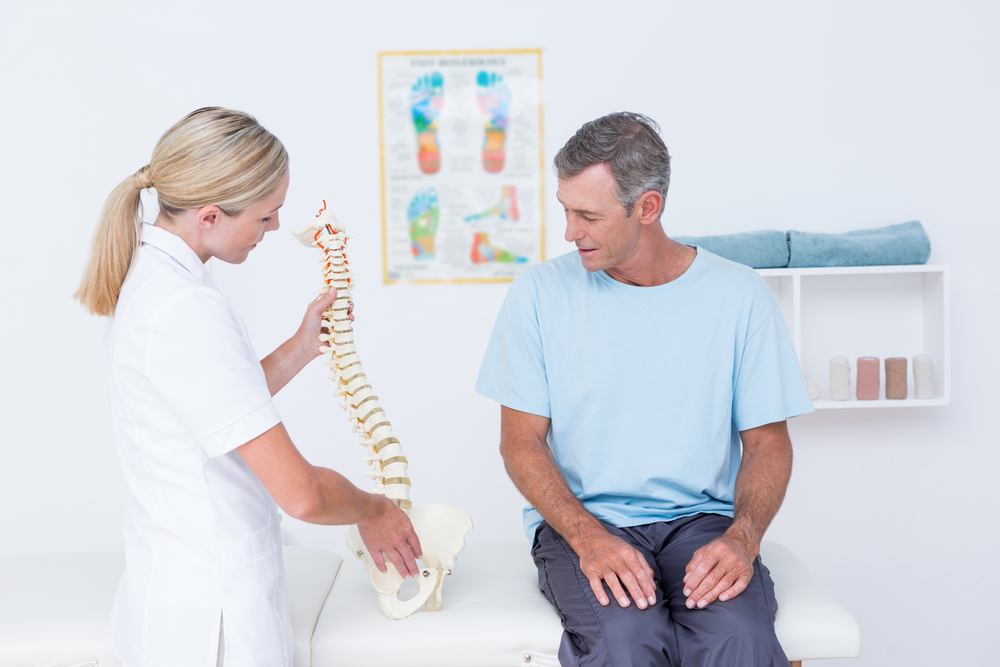 Doctor showing anatomical spine to her patient in medical office